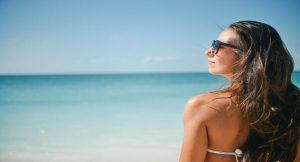 אישה מביטה הצידה בחופשה בחול בים
