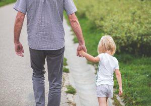 ילדה ואבא מטיילים בחוות עיזים